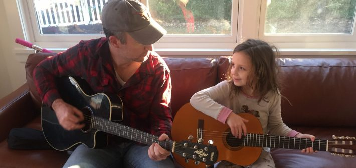 Shawn Brimley teaching Claire to play the guitar