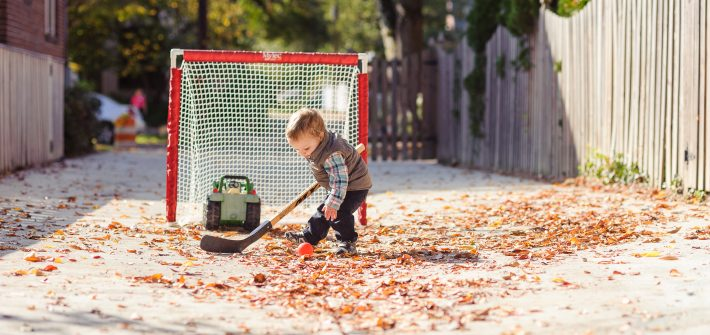 Tommy Brimley playing hockey in alley by Brimley house