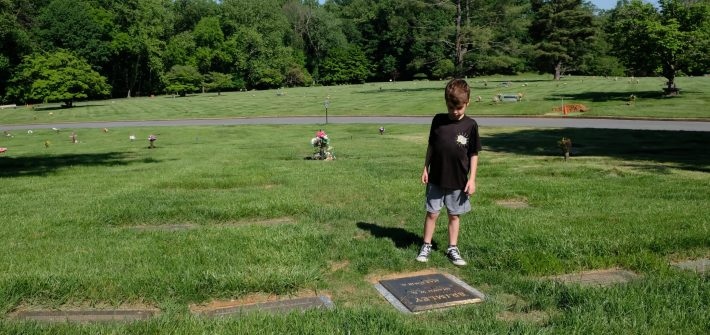 Austin Brimley looking at Shawn Brimley's grave outside DC