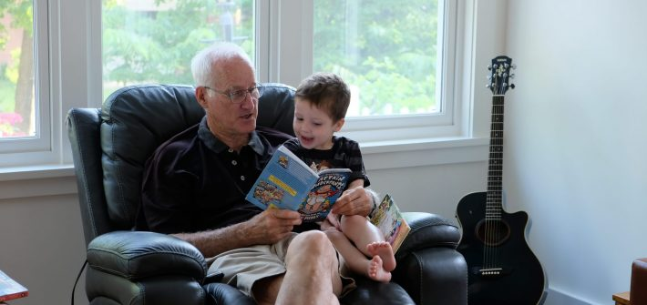 Grandpa Tom Clark reads a book to Tommy Brimley