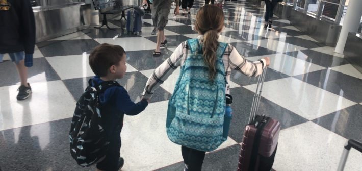 Claire Brimley holding Tommy's hand in the airport