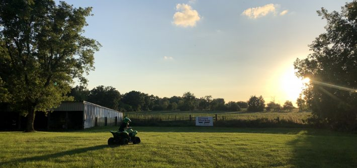 Austin Brimley riding an ATV in a field in Michigan with the sun setting