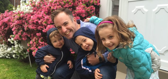 Shawn Brimley and his three children hugging in front of their DC home