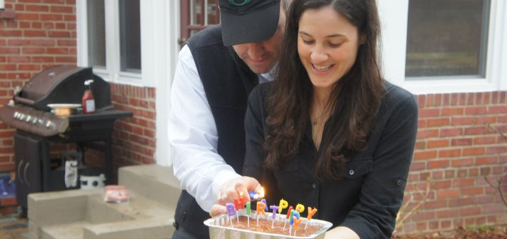 Shawn and Marjorie Brimley lighting candles for birthday party in DC backyard