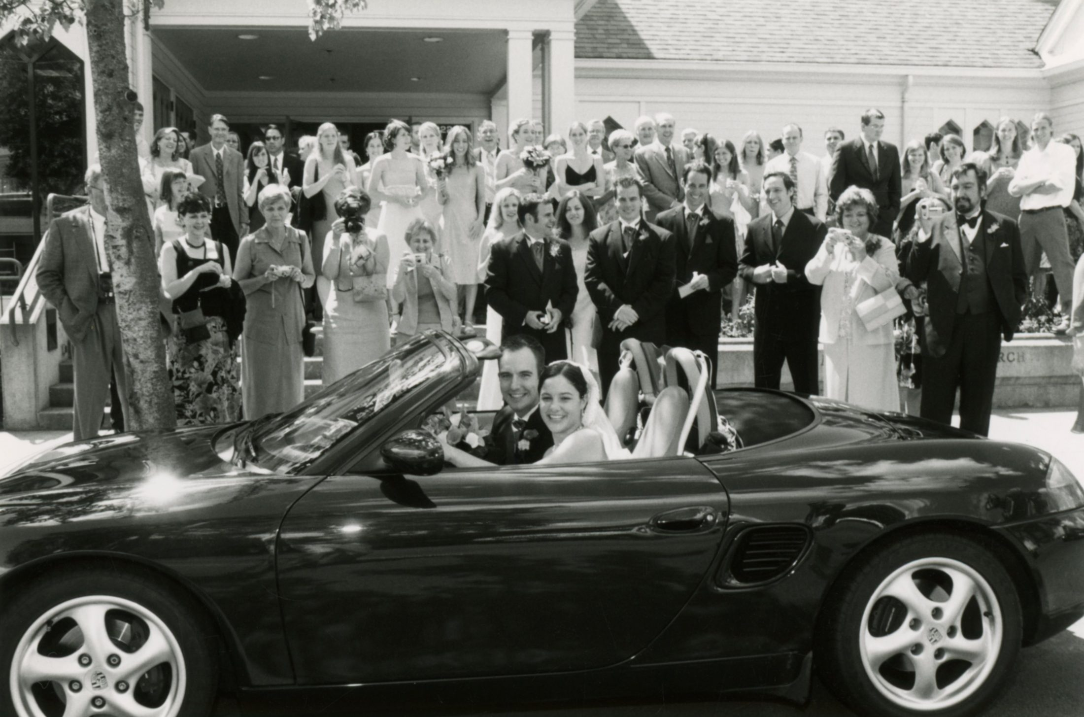 Shawn and Marjorie Brimley in car after wedding surrounded by family and friends