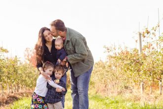 DC widow blog writer Marjorie Brimley is kissed by her husband and hugged by her children in a field