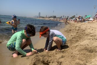 Children of DC widow blog writer Marjorie Brimley build a sandcastle on the beach