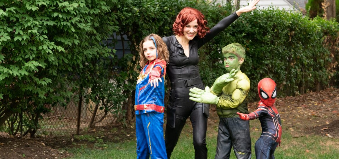 DC widow blog writer Marjorie Brimley dressed as Black Widow with her children dressed as the Avengers stand in yard
