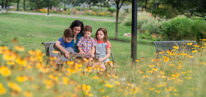DC widow blog writer Marjorie Brimley on bench with children and flowers