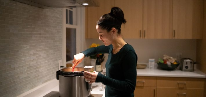 DC widow blog writer Marjorie Brimley cooks over a stove in a kitchen